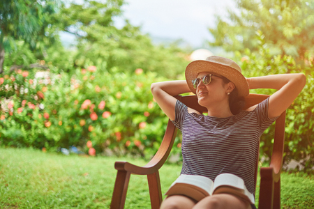Summer vacation concept. Young woman sitting in backyard Stockfoto