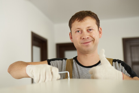 Man putting screw in furniture and showing thumb up in camera Stok Fotoğraf