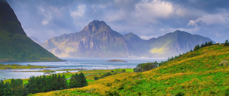 Lofoten islands on summer day. Norway landscape of summer nature. Sun illuminate beautiful Lofoten mountains.