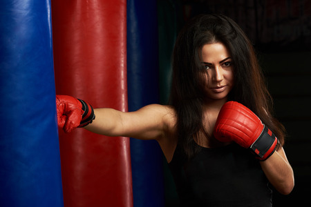 Young girl punching boxing bag. Boxing fitness theme
