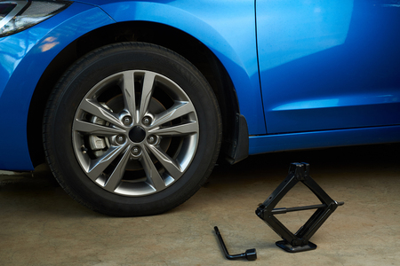 Tools for replacing car wheel on modern car background