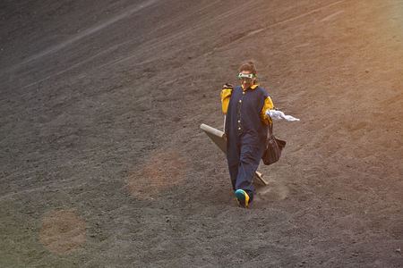 Woman walk with volcano board on ash stones in Nicaragua