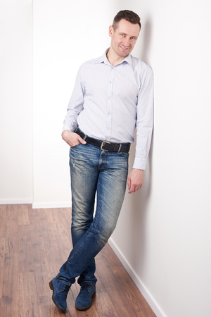 Positive smiling young man in casual outfit standing in office Stock Photo