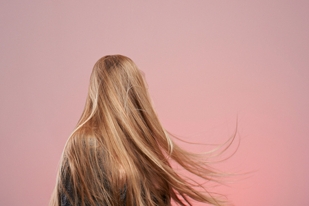 Long blonde woman hair isolated on pink background