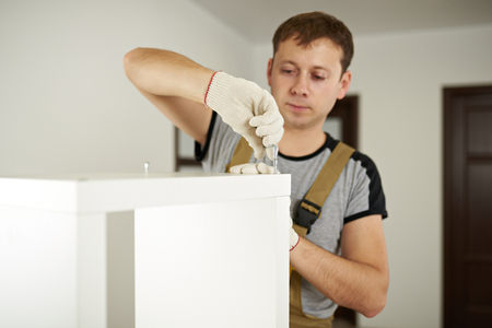 Worker putting screw in white cabinet. Carpenter service theme