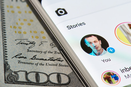 New york, USA - April 11, 2018: Instagram story on smartphone close-up on dollar currency background