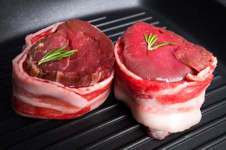 Filet mignon wrapped in fresh bacon on pan close-up. Fresh raw beef meat. Stockfoto - 100107892