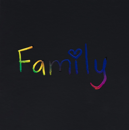 Family word hand written on black paper background