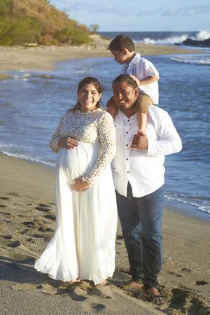 Portrait of hispanic family on beach waiting for new baby