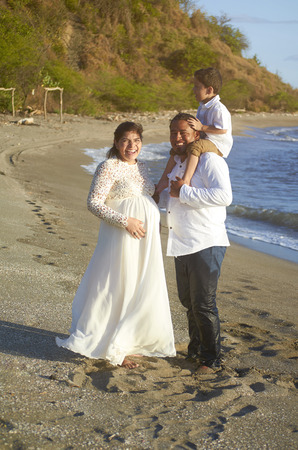 Happy smiling hispanic family stand on beach sunset time