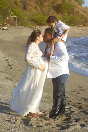 Family kiss on beach in sunset background. Happy pregnancy theme Stock Photo