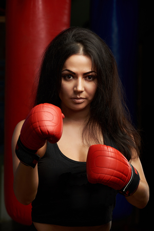 Portrait of sexy brunette in boxing gloves. Woman boxing concept