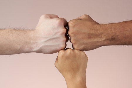 Hands fists together of different color skin people isolated on brown background Imagens