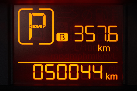 Digital screen in car with yellow numbers close-up view