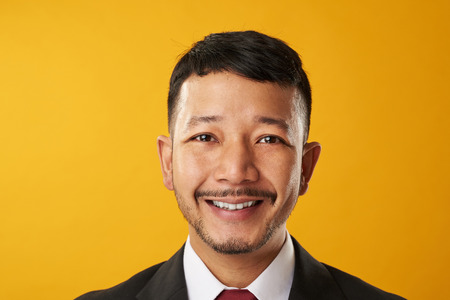 Happy smiling asian business man headshot portrait isolated on yellow background Stock Photo