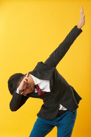 Junger asiatischer Mann, der Tupferhaltung lokalisiert auf gelbem Hintergrund zeigt Standard-Bild