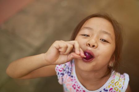 Aziatisch meisje eet ijs op stok boven bovenaanzicht