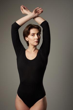 Calm pretty woman in body wear on grey background