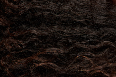 Texture of dark woman wavy curly hair close up view