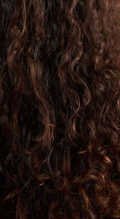 Pattern of brown curly woman hair. Natural woman hair background