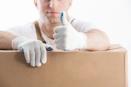Professional help with relocation. Thumb up of worker with gloves on white background.