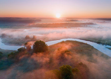 Summer aerial landscape. Sunrise over fog and river. Misty meadow in warm sunlight.
