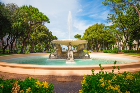 Central park of Rimini. Italy. Rimini city center with fountain and green trees.