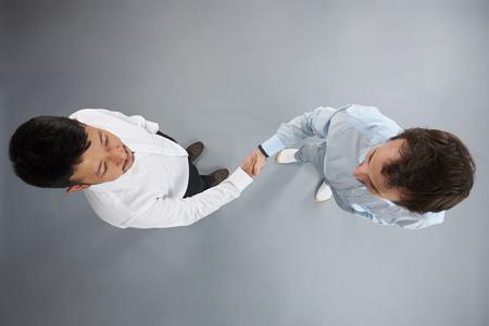 Stretta di mano di due uomini sopra vista superiore isolata su sfondo grigio