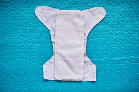 Reusable clean cloth diaper open and lay on green blanket 免版税图像
