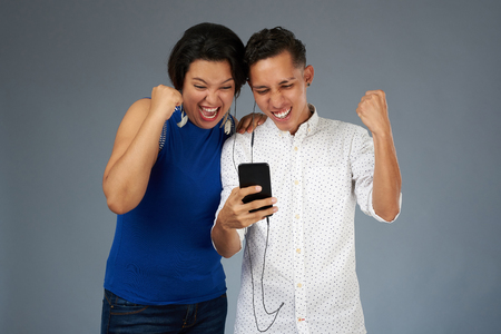 Happy young couple with smartphone isolated on gray studio background