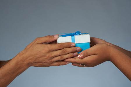Hands holding blue gift box close up view on gray studio background Stock Photo
