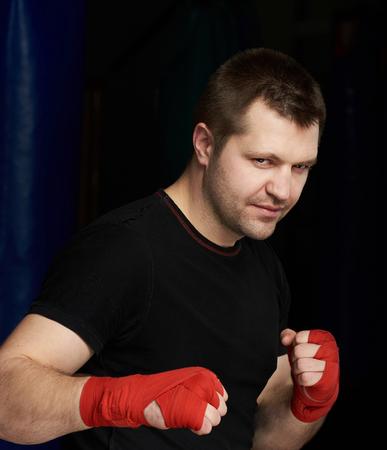 Portrait of kickboxing caucasian man wearing red hand bandage