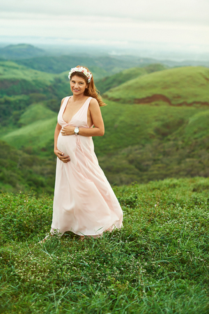 A pretty young pregnant woman standing on natural background Stock Photo