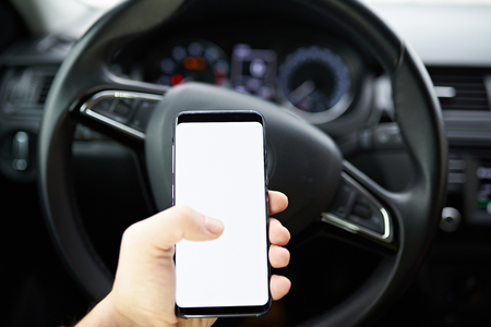 Using smartphone while driving. Cellphone in hand mockup on blur car background Фото со стока