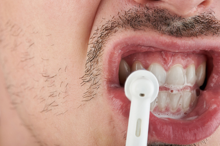 Morning routine theme. Close up of man cleaning teeth