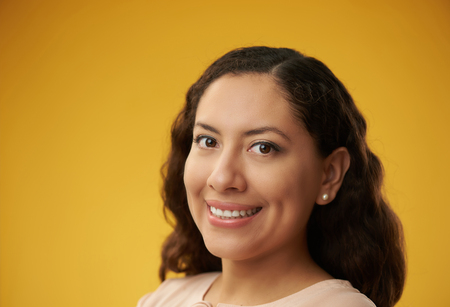Latina girl smiling. Headshot of dark hair woman on yellow color background