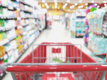Supermarket retail theme. Blurred shop rows with cart