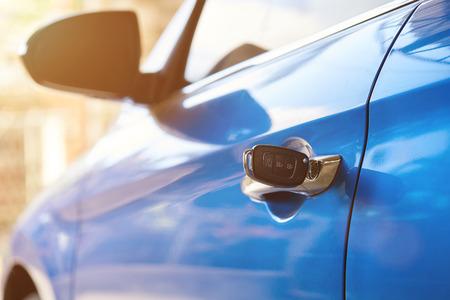 Poignée de véhicule argentée avec gros plan de clé sur fond de journée ensoleillée Banque d'images
