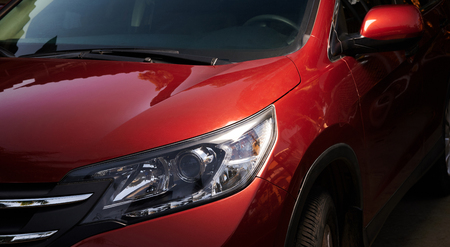 Modern red car headlight. Cleaning car theme