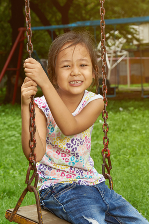 Asian girl smiling on a swing. Filipina girl. Banque d'images