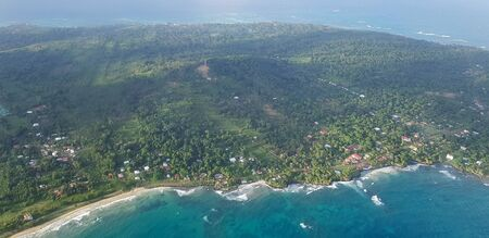 Green island in blue ocean water above top view