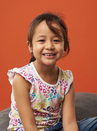 Asian kid smiling portrait. Color background. 스톡 콘텐츠