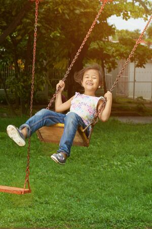 Asian kid in playground hang on swings in sunny bright day background