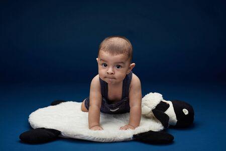 Latin baby boy portrait in blue studio  background