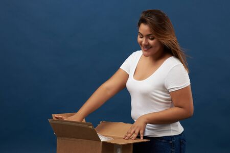 Young woman unboxing package isolated on blue studio background Reklamní fotografie