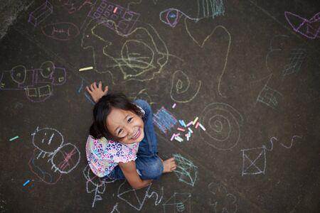 Chica asiática dibujando con tiza sobre asfalto. Dibujos de tiza de un niño filipina. Niña filipina de 7 años jugando con tiza.