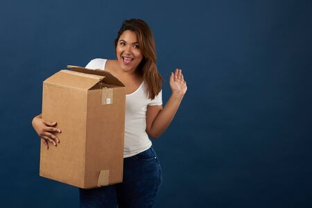 Teenager girl with big package box isolated on blue studio background