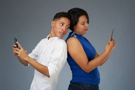 Young people with smartphones on gray studio background Stock Photo