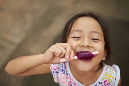 Asian girl eating ice cream in outdoor. Filipina kid eating an ice cream and staring at camera. Standard-Bild
