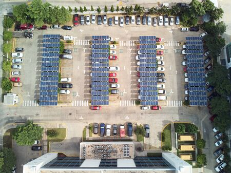 Parking lot with solar panels for charging cars above top view